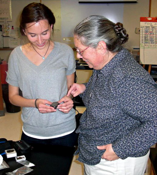 Carolyn showing a meteorite to teacher.