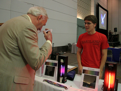 UM President Mote visits the Astro Department's booth.