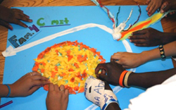 photo of childrens' hands on a poster model of a comet orbit