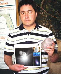Visitor to Ft Lauderdale Museum of Discovery and Science holding a Comet Litho and 3D model of Tempel 1.